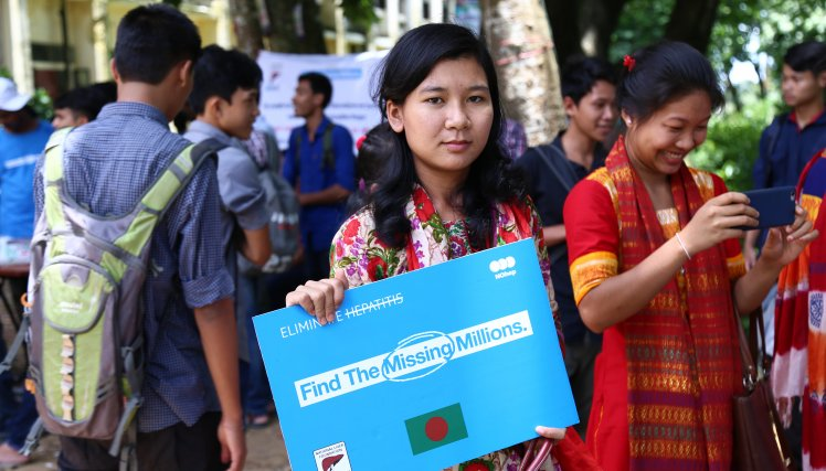 "A ""Chakma"" student holding a ""Find the Missing Millions"" board to support the initiative. The Chakma tribe is the largest indigenous tribe in Bangladesh. They live in Rangamati, Chittagong hill tracts which is in the South-East Bangladesh."